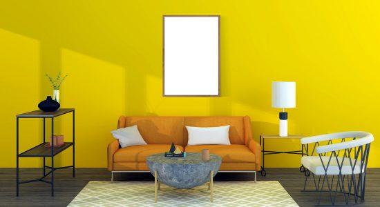 Salon décoré et composé d'un canapé, d'un fauteuil et d'une table basse avec un mur jaune au fond
