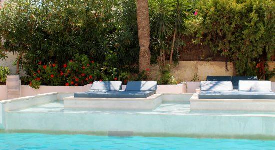Des banquettes lit au bord d'une piscine